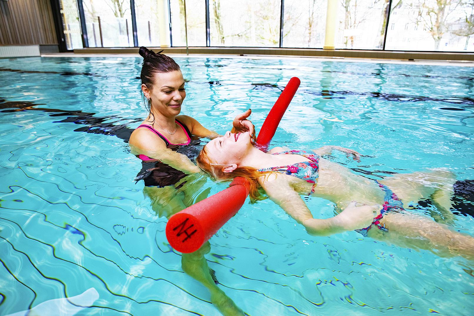 Kvinna hjälper ungdom att träna simning.