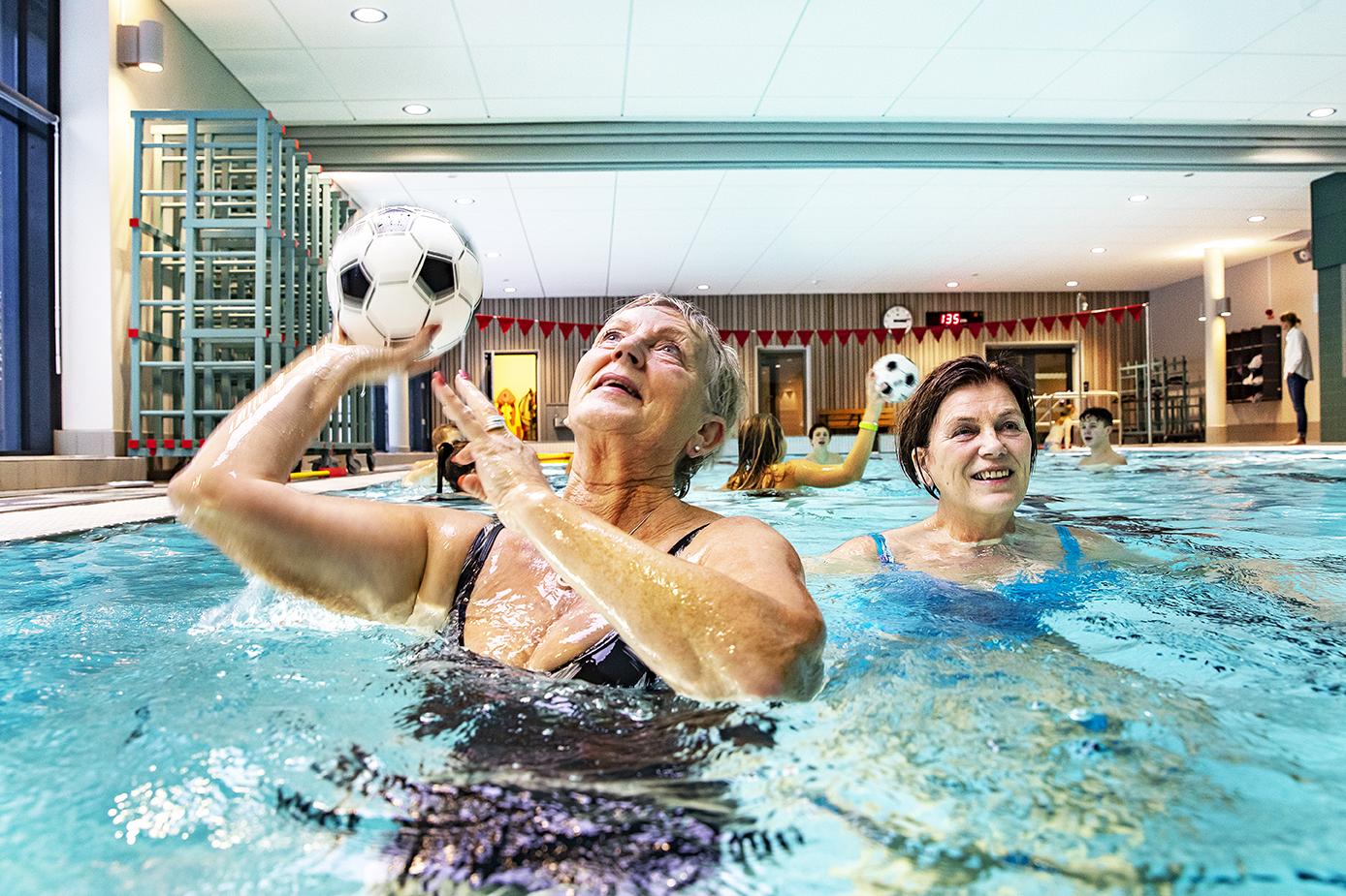 Kvinnor kastar boll i poolen-
