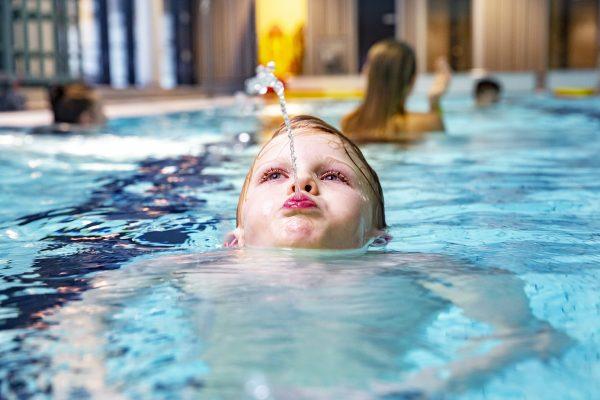 Pojke simmar och blåser en vattenstråle ur munnen.