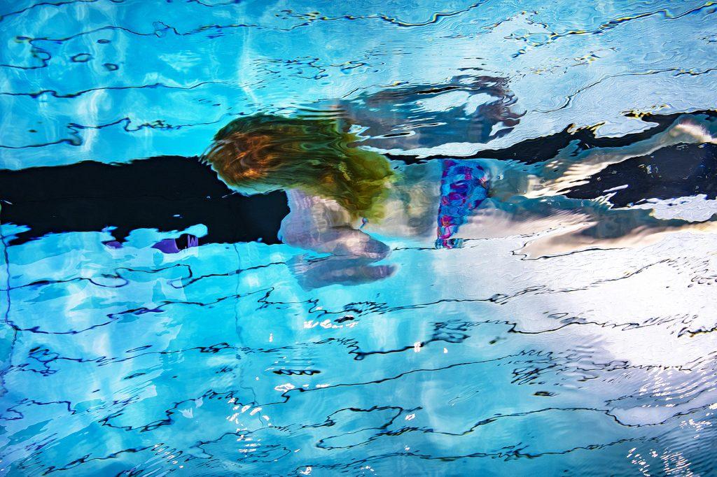 Flicka simmar under vatten.