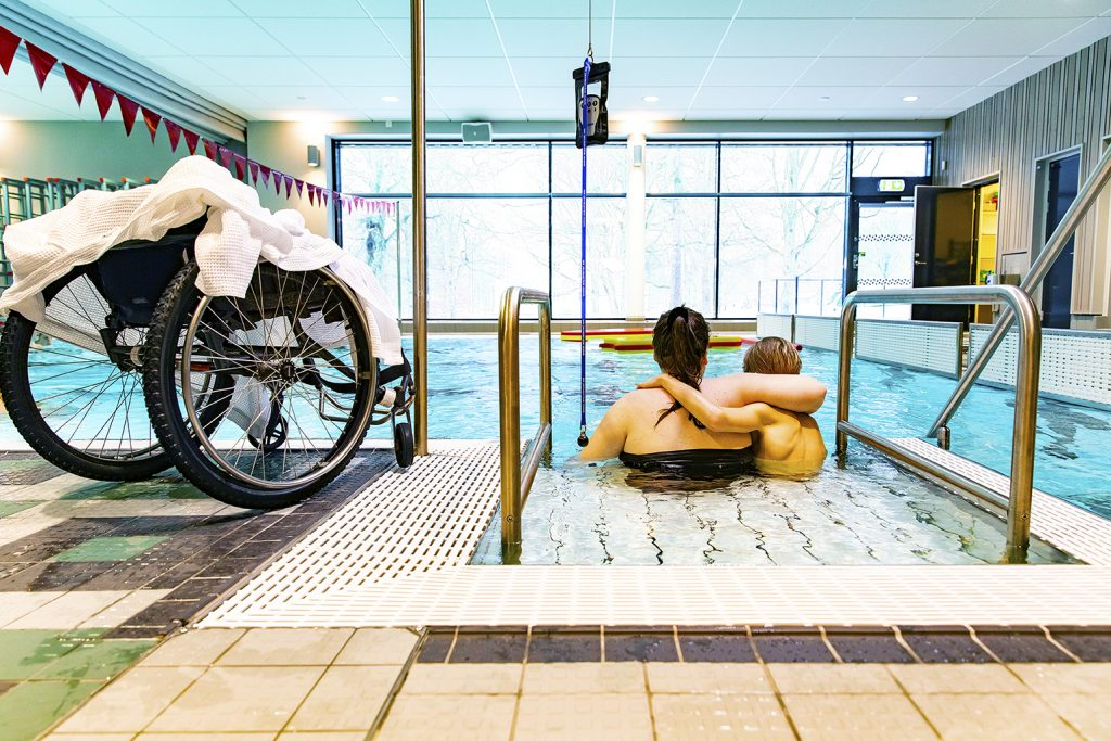 Mamma hjälper funktionshindrad pojke att ta sig ner i bassäng.