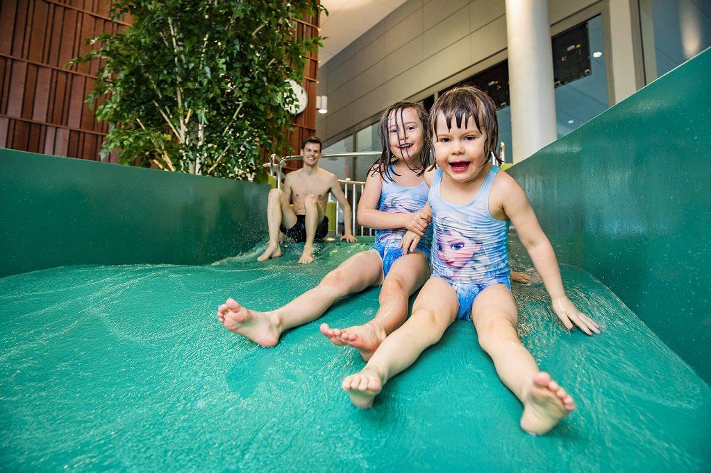 Två flickor/barn åker rutschbana.
