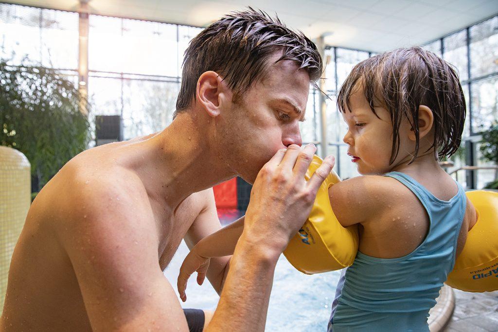 Pappa blåser upp arm-badringar för dotter