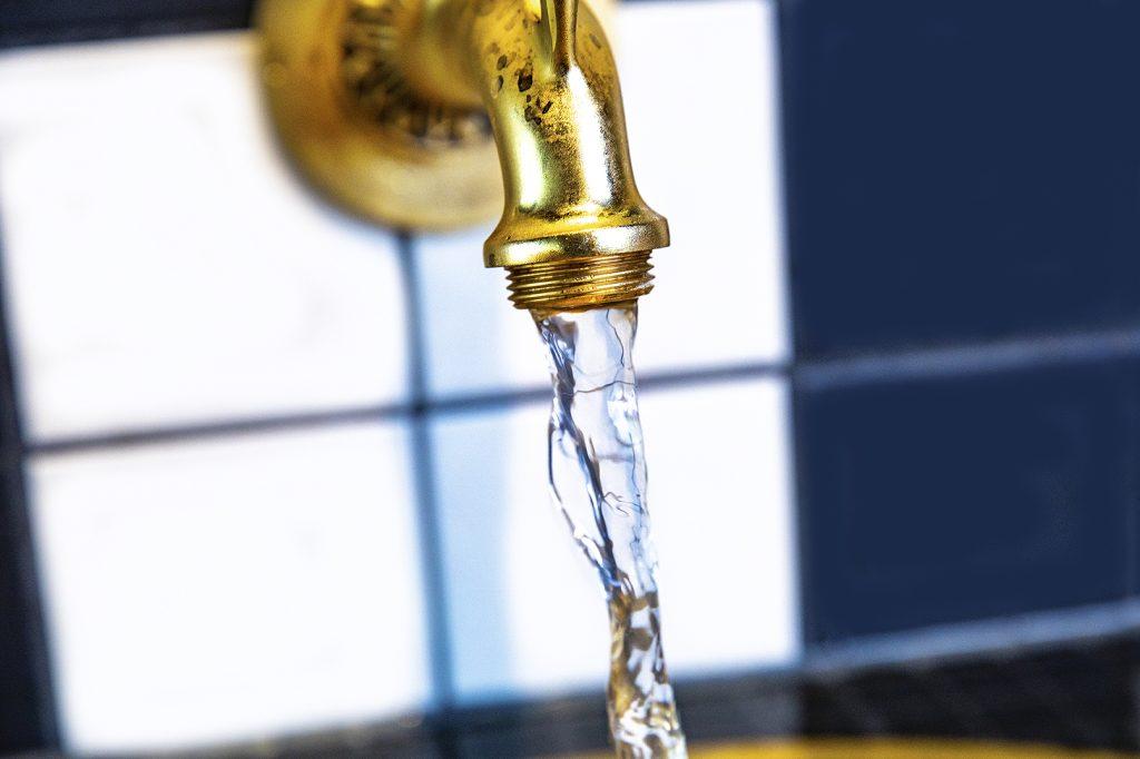 Vatten rinner ur förgyld kran.