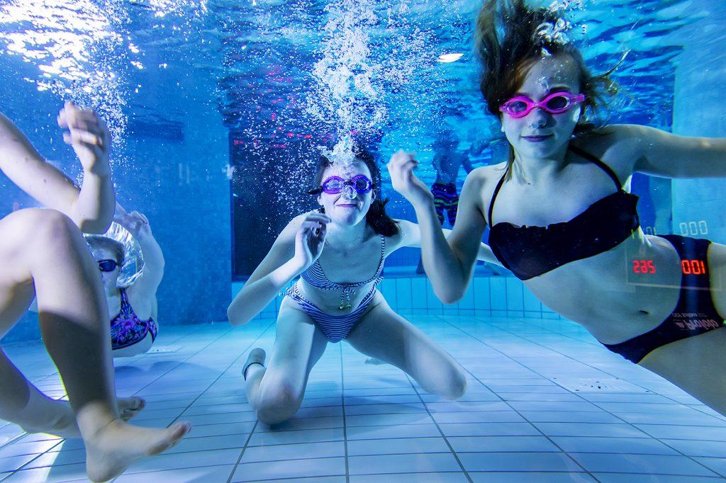 Tjejer simmar under vattnet.
